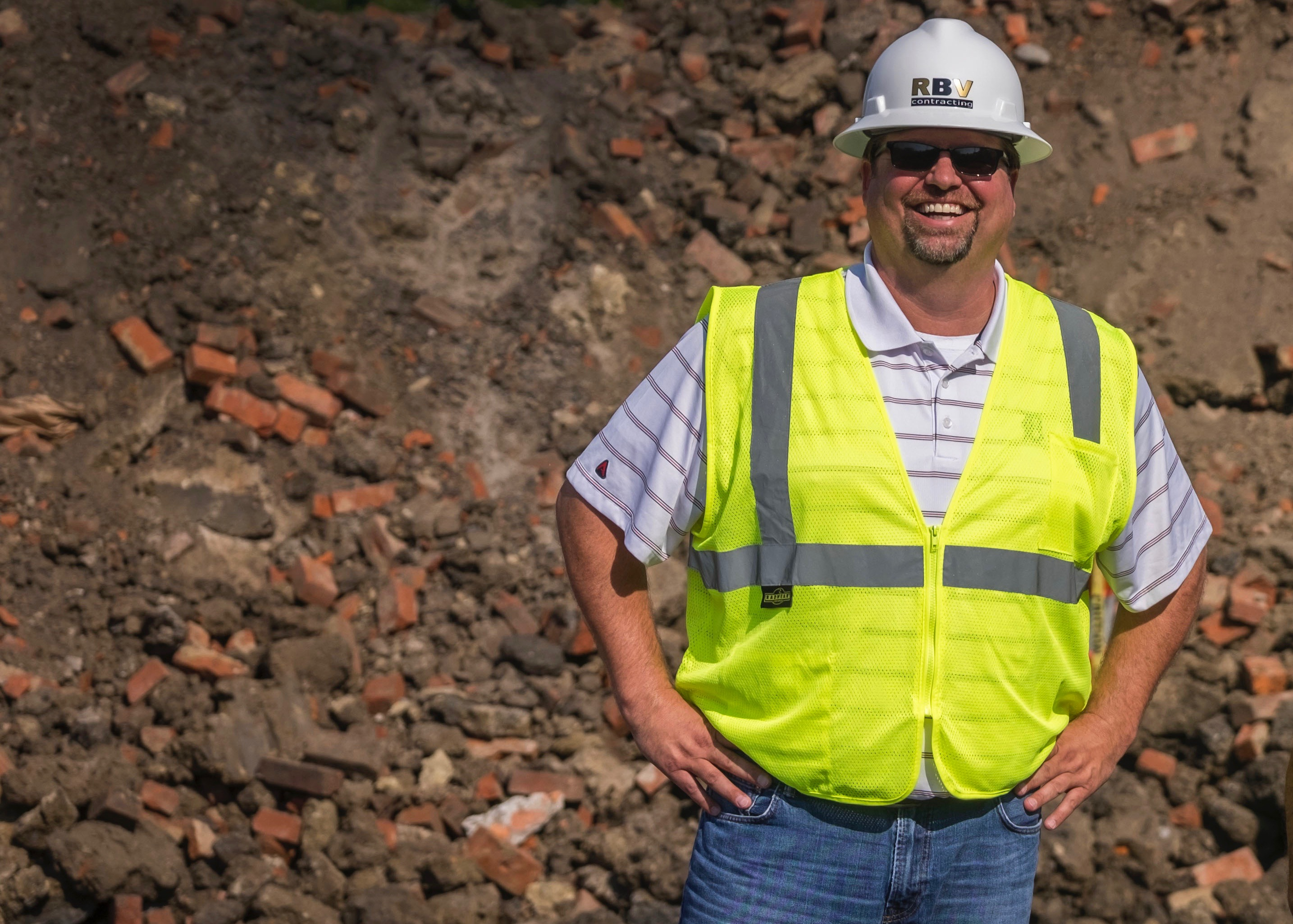 Jim Foucher, the vice president, smiles while wearing a safety vest and hardhat on the job site at Elton Park