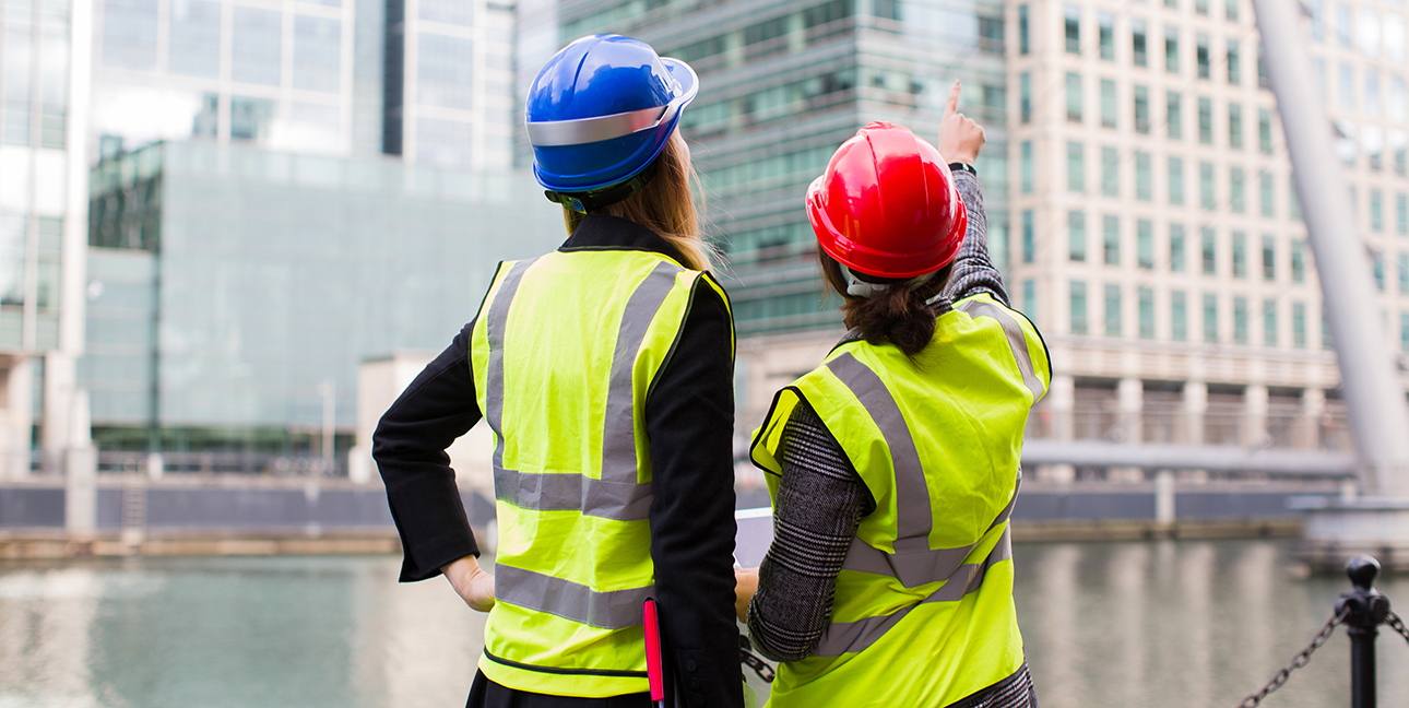 Two women in safety vests and hardhats point at a construction site