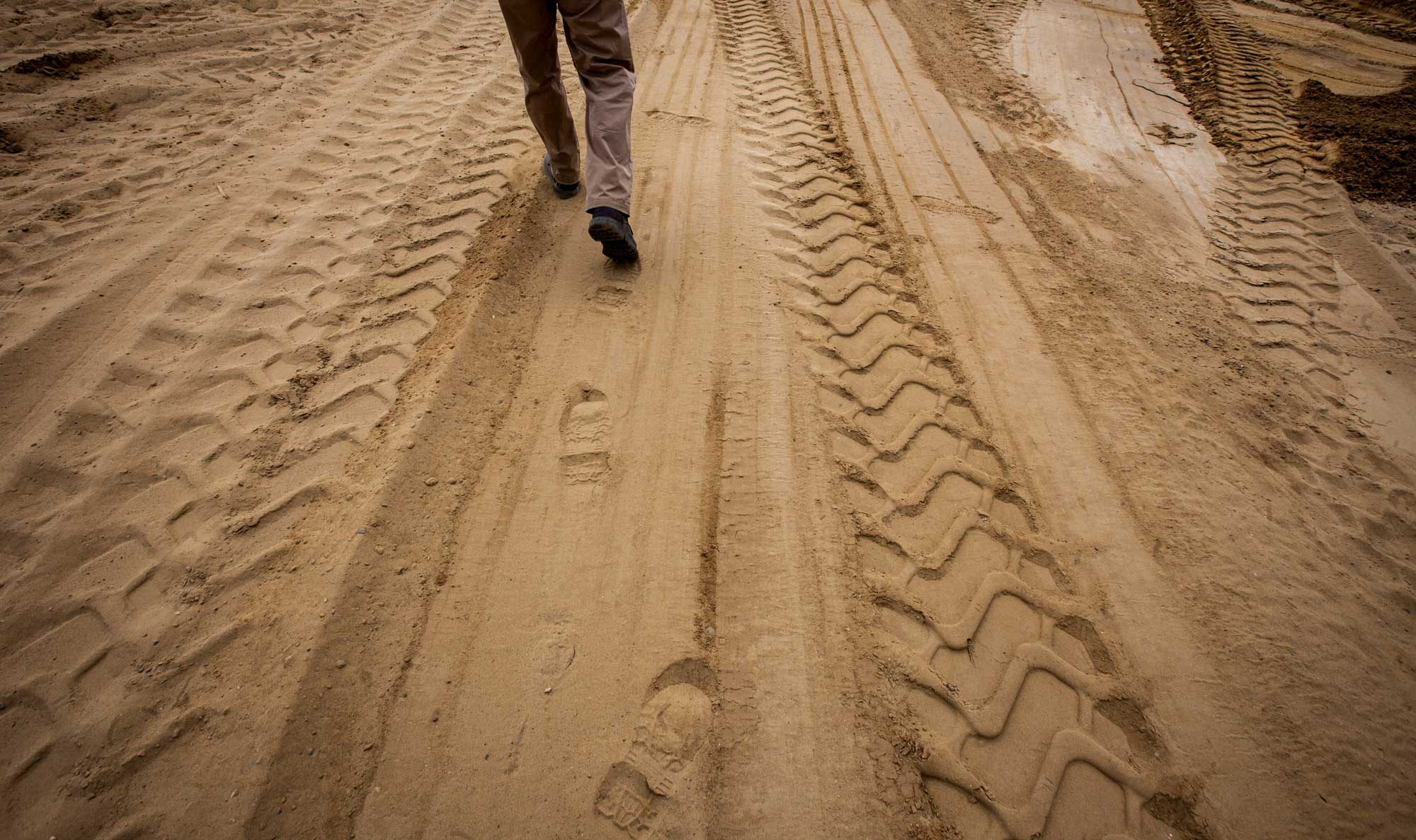 An RBV Contracting employee walks in the dirt, leaving footprints alongside the tire marks from construction equipment.