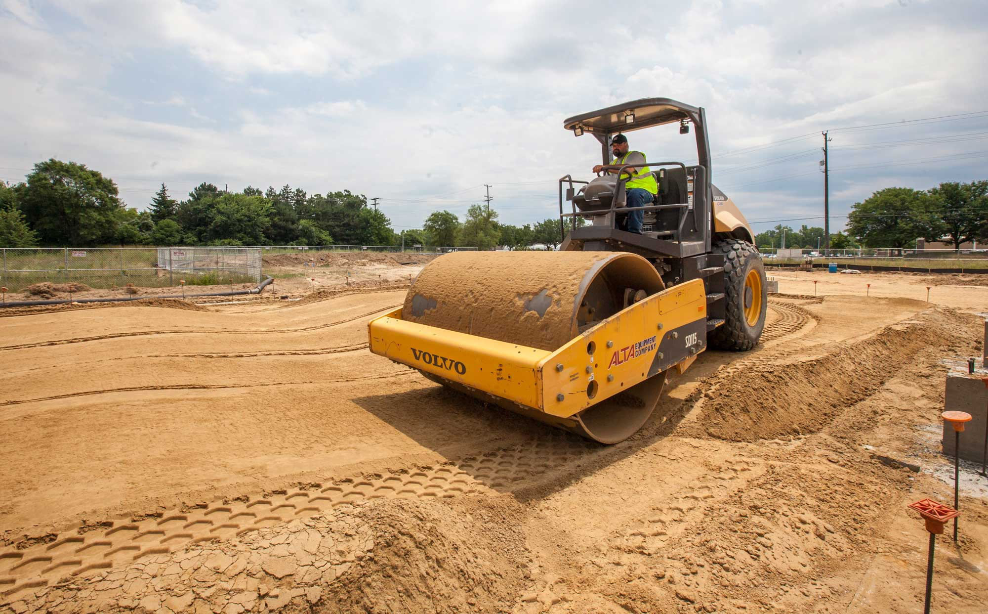 An RBV employee drives a steamroller across a job site